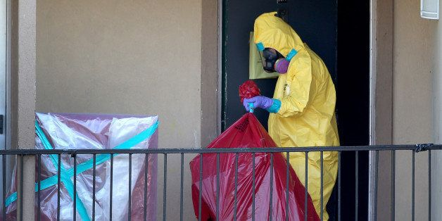 DALLAS, TX - OCTOBER 06:  A member of the Cleaning Guys Haz Mat clean up company removes items from the apartment where Ebola patient Thomas Eric Duncan was staying before being admitted to a hospital on October 6, 2014 in Dallas, Texas. The first confirmed Ebola virus patient in the United States was staying with family members at The Ivy Apartment complex before being treated at Texas Health Presbyterian Hospital Dallas. State and local officials are working with federal officials to monitor other individuals that had contact with the confirmed patient.  (Photo by Joe Raedle/Getty Images)