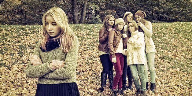 This is a major issue in school, rejection and intimidation between students. Here is a group of five friends gossiping behind the back of a visibly sad rejected girl. Desaturated effect.