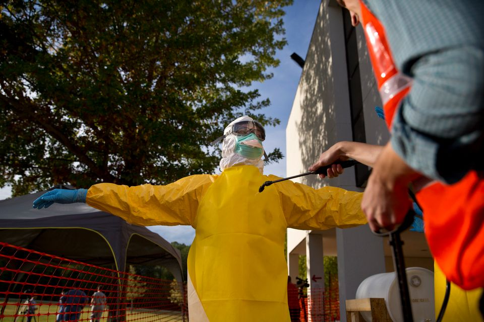 Licensed clinician Dennis Salter is decontaminated before disrobing at the end of the simulated training session on Monday, O