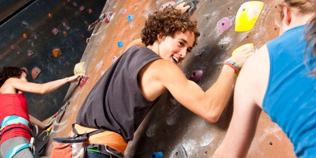 Three happy teenagers having fun at rock climbing wall