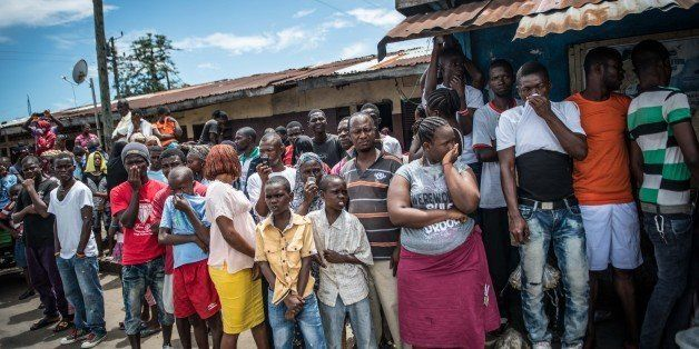 MONROVIA, LIBERIA - OCTOBER 15: People crowd watch Red Cross members as they carry dead body of Mambodou Aliyu (35) died due to the Ebola virus, in Monrovia, Liberia on 15 October, 2014. (Photo by Mohammed Elshamy/Anadolu Agency/Getty Images)