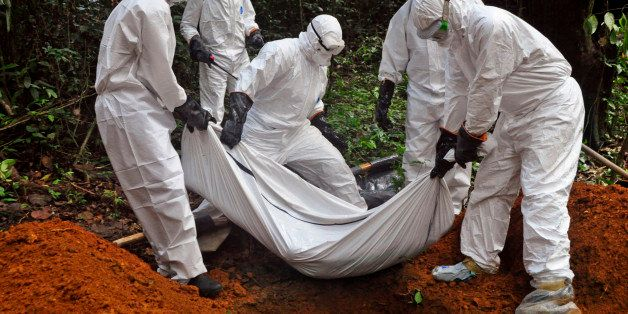 """Health workers bury the body of a woman who is suspected of having died of the Ebola virus in Bomi county, on the outskirts of Monrovia, Liberia, Monday, Oct. 20, 2014. Liberian President Ellen Johnson Sirleaf said Ebola has killed more than 2,000 people in her country and has brought it to """"a standstill,"""" noting that Liberia and two other badly hit countries were already weakened by years of war. (AP Photo/Abbas Dulleh)"""