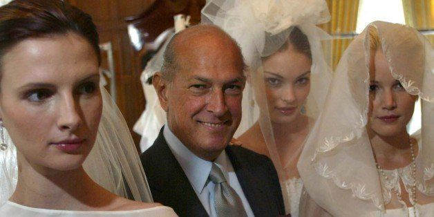 Designer Oscar de la Renta is flanked by models wearing wedding dresses from his first bridal collection in New York, Monday Oct. 7, 2002. From left are Elodie, de la Renta, Valentina, and Brooke. (AP Photo/Stuart Ramson)