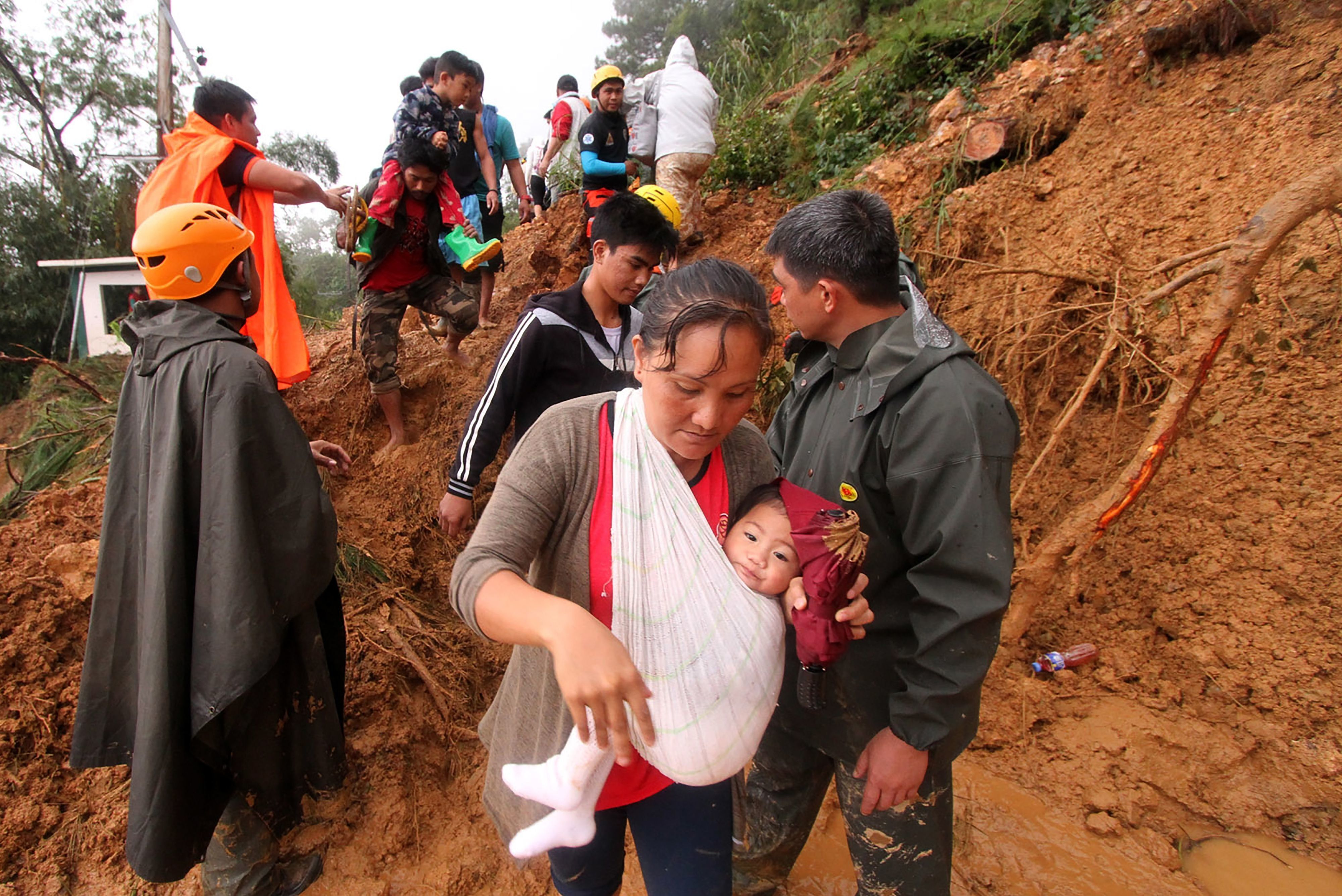 Families and relatives of miners move to safer grounds after massive landslides triggered by Super Typhoon Mangkhut in Itogon town, Benguet province on September 16, 2018. - Typhoon Mangkhut rocked Hong Kong en route to mainland China on September 16, injuring scores and sending skyscrapers swaying, after killing at least 30 people in the Philippines and ripping a swathe of destruction through its agricultural heartland. (Photo by JJ LANDINGIN / AFP)        (Photo credit should read JJ LANDINGIN/AFP/Getty Images)