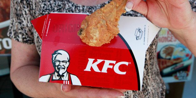 A customer hold a piece of Kentucky Fried Chicken outside a KFC restaurant, Tuesday, July 13, 2010, in Mountain View, Calif. Yum Brands Inc., which owns Taco Bell, Pizza Hut and KFC, reports second-quarter results after the close of regular trading. (AP Photo/Paul Sakuma)