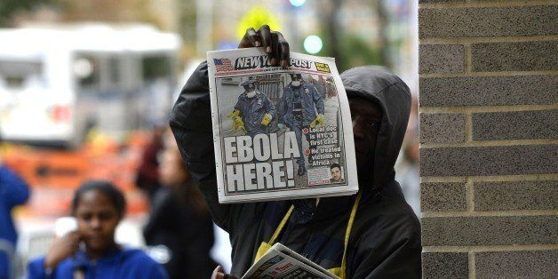 A newspaper vendor holds up a copy of the NY Post  in front of the  entrance to  Bellevue Hospital October 24, 2014 in New Yo