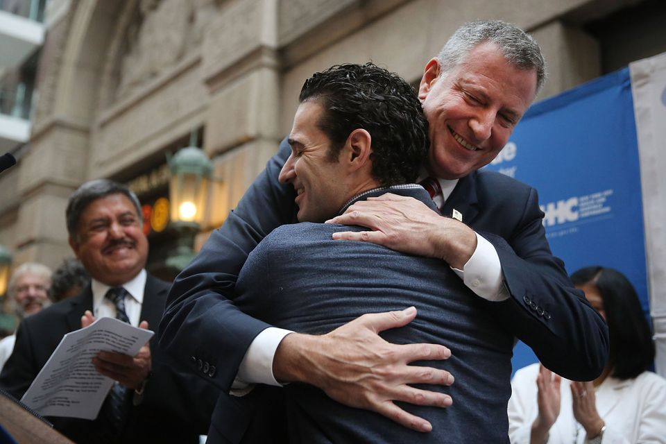 Dr. Craig Spencer, who was diagnosed with Ebola in New York City last month, hugs New York Mayor Bill de Blasio at a news con