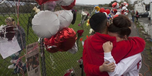 MARYSVILLE, WA - OCTOBER 26: Members of the community and students grieve beside a makeshift memorial at Marysville-Pilchuck High School on October 26, 2014 in Marysville, Washington. High school freshman Jaylen Fryberg shot five students at the high school's cafeteria, injuring four, killing one and then killing himself on October 24th. (Photo by David Ryder/Getty Images)