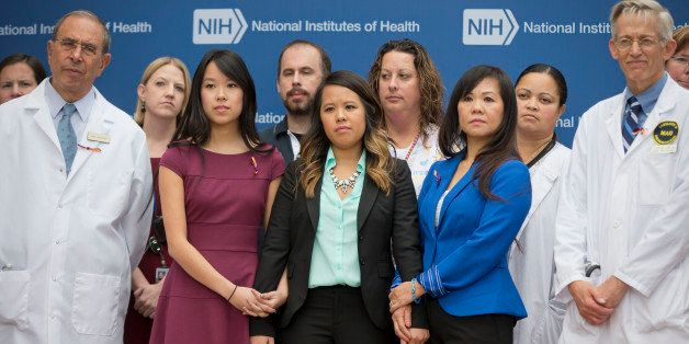 Patient Nina Pham, center, with her mother Diana Berry, right, and sister Cathy Pham, left,  and members of the NIH staff outside during a news conference at NIH in Bethesda, Md., Friday, Oct. 24, 2014. Pham, the first nurse diagnosed with Ebola after treating an infected man at a Dallas hospital is free of the virus. The 26-year-old Pham arrived last week at the NIH Clinical Center. She had been flown there from Texas Health Presbyterian Hospital Dallas. (AP Photo/Pablo Martinez Monsivais)