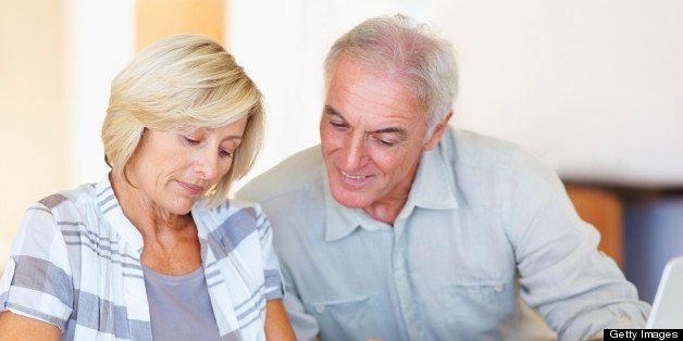 Happy senior couple budgeting their monthly expenses using calculator at home