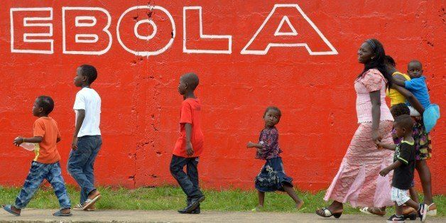 Young women and children walk past a slogan painted on a wall reading 'Ebola' in Monrovia on August 31, 2014. Liberia on August 30, 2014 said it would deny permission for any crew to disembark from ships at the country's four seaports until the Ebola epidemic ravaging west Africa was under control. AFP PHOTO/DOMINIQUE FAGET        (Photo credit should read DOMINIQUE FAGET/AFP/Getty Images)