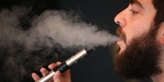 LONDON, ENGLAND - AUGUST 27:  Vape Lab employee Leonardo Verzaro uses an E-Cigarette while working on August 27, 2014 in London, England. The Department of Health have ruled out the outlawing of 'e-cigs' in enclosed spaces in England, despite calls by WHO, The World Health Organisation to do so. WHO have recommended a ban on indoor smoking of e-cigs as part of tougher regulation of products dangerous to children.  (Photo by Dan Kitwood/Getty Images)