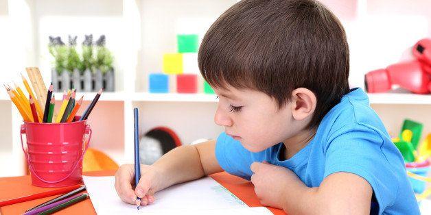 cute little boy drawing in his...