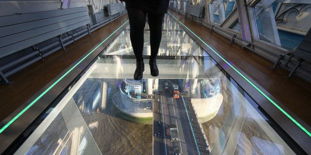LONDON, ENGLAND - NOVEMBER 10:  A visitor crosses Tower Bridge's new glass walkway on November 10, 2014 in London, England. Unveiled today the glass floor panels along the bridge's high-level walkways weigh 300 kgs each, cost ᅢツᅡᆪ1m and will give visitors a new view over the historic bridge crossing The River Thames.  (Photo by Peter Macdiarmid/Getty Images)