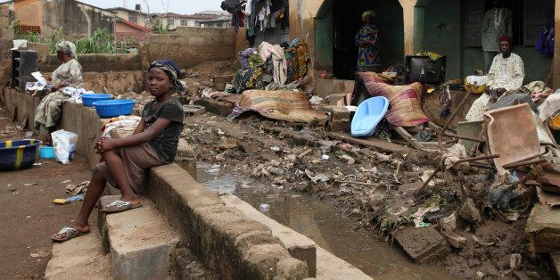 Residents sit outside their flooded home  in Ibadan, Nigeria , Friday, Sept 2, 2011. Flash flooding across Nigeria's southwest killed at least 102 people in the last week, the country's Red Cross said .Some 1,500 people remain displaced by the torrential downpours, officials said.The major flood hit hardest in Oyo state's capital of Ibadan. Heavy rains there on Friday made a local dam overflow, sending water crashing through the informal settlements surrounding the city. The water also damaged three bridges in the area, trapping people in their neighborhoods. (AP Photo/Sunday Alamba)