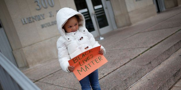 WASHINGTON, DC - NOVEMBER 25:  4 year old Marley Hendrix Totten joins a group of protesters as they gather outside the headquarters of the Washington DC Metropolitan Police Department as part of a planned '28 Hours for Mike Brown' protest November 25, 2014 in Washington, DC. Protests have taken place across the United States in the wake of a Ferguson, Missouri grand jury's decision not to indict police officer Darren Wilson in the fatal shooting of 18 year old Michael Brown.  (Photo by Win McNamee/Getty Images)