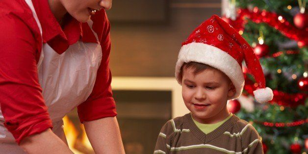 Mother and son making christmas cake, son watching mum's hand, smiling.?