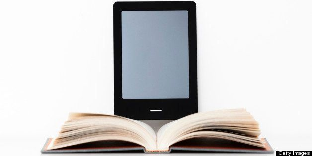E-reader digital tablet resting on a shelf beside an open traditional paper book.