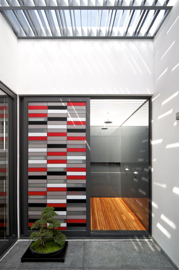 A shower is connected to a patio and features an open-air ceiling only partially covered with slats.