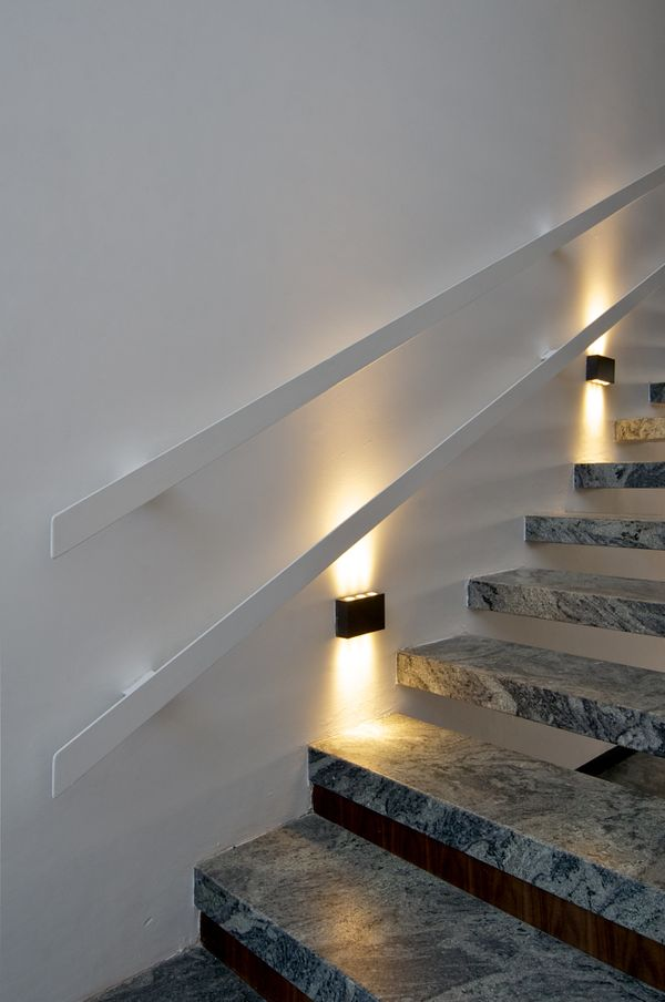 Low lighting fixtures below the railing make sure to emphasis the beautiful marble stairs that people might overlook.