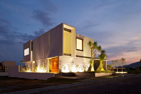 At night, the house is mind-blowing. Under-lights shine a spotlight on impeccable landscaping and makes the home look almost
