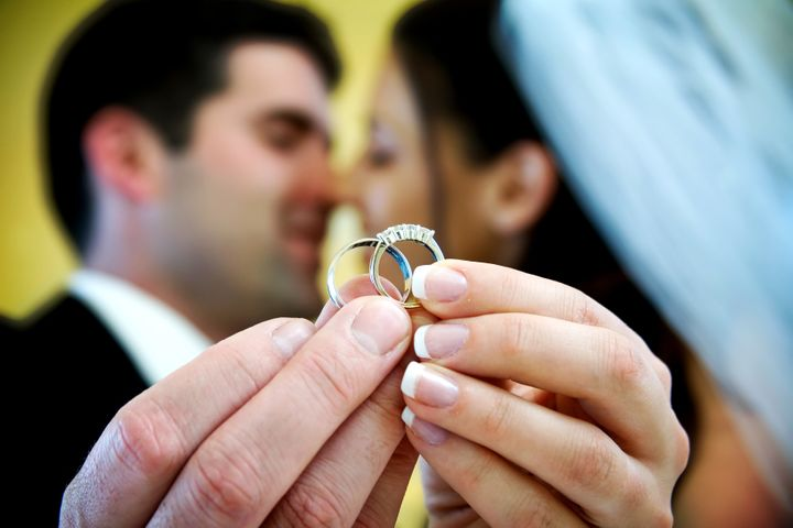 The bride and groom are holding up the wedding rings and kissing in the background. NOTE: this photo has a very shallow depth of field