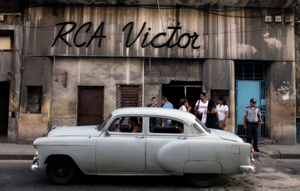A taxi driver takes passengers in a classic car as people line up to buy a cup of coffee from a vendor's home, formerly the R