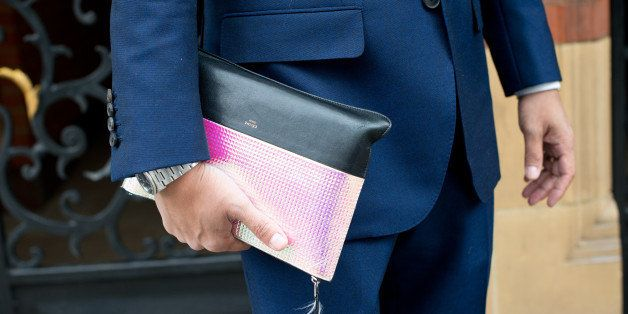 LONDON, ENGLAND - JUNE 16: Fashion Writer Tahmo Ogasawara wears a bespoke suit and Celine clutch on day 2 of London Collectio
