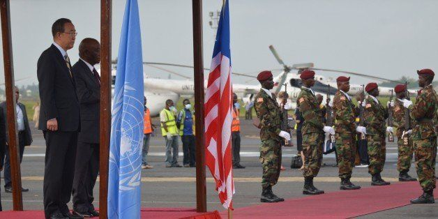 UN chief Ban Ki-moon (L) reviews the troops with Liberian Vice President Joseph Boakai after arriving at the Monrovia airport, on December 19, 2014, on the first stop of a visit to Ebola-ravaged west African countries for a first-hand assessment of global efforts to fight the epidemic.     AFP PHOTO ZOOM DOSSO        (Photo credit should read ZOOM DOSSO/AFP/Getty Images)