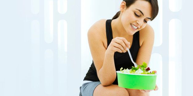 Young woman holding a salad to take away: healthy eating concept.