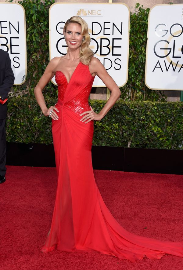 Klum is giving new meaning to lady in red. She looks red hot in this one-shouldered gown with a long train. Her retro waves c