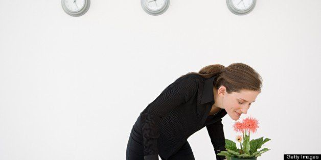 Businesswoman smelling a flower