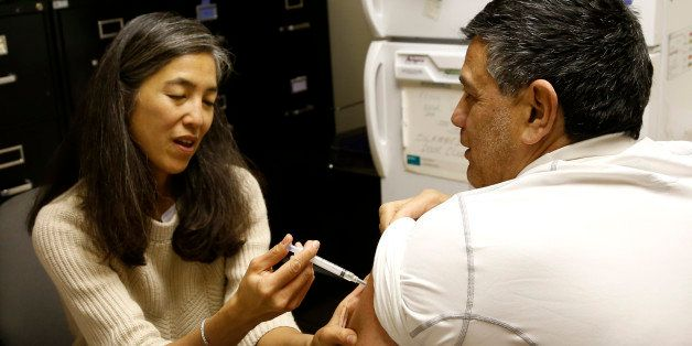 Dr. Julie Morita, Director of Immunizations at the Chicago Dept. of Public Health, gives Gary Chavarria a flu shot at a North Side clinic Friday, Jan. 11, 2013, in Chicago. Illinois is among the 24 states across the nation hardest hit by the flu, but vaccine is still available in most locations, health officials said Friday as they urged people to get their shots. (AP Photo/Charles Rex Arbogast)