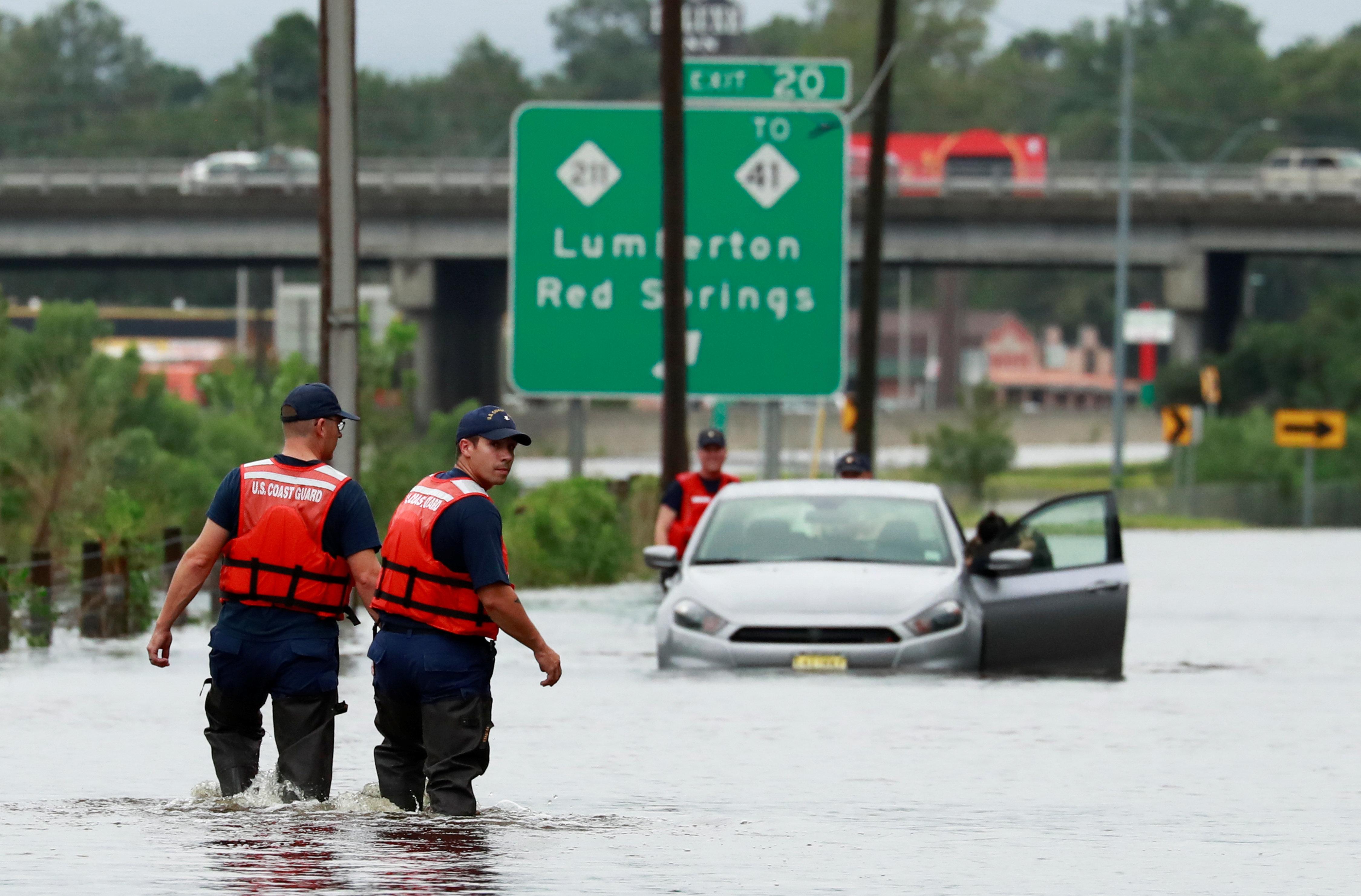 Members of the Coast Guard help a stranded motorist in the flood waters caused by Hurricane Florence in Lumberton, North Carolina, U.S. September 16, 2018. REUTERS/Jason Miczek