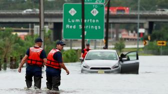 Members of the Coast Guard help a stranded motorist in the flood waters caused by Hurricane Florence in Lumberton, North Carolina, U.S. September 16, 2018. REUTERS/Jason Miczek
