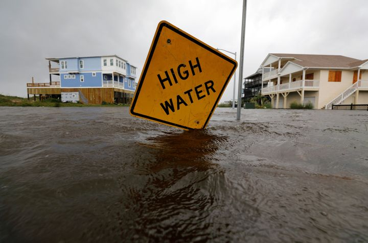 Flood waters lap at a high water warning sign that was partially pushed over by Hurricane Florence on Oak Island, North Carol