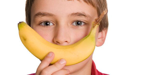 'A primary school aged boy is happy to eat a healthy banana. Isolated on a clean white background. Adobe RGB 1998 profile. Part of a larger set of images related to education, children and healthy eating.'