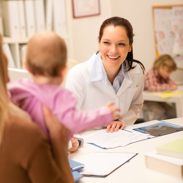 Female pediatrician smiling at baby patient sitting behind office desk
