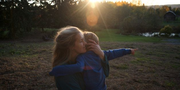 Mother holds son on grassy hill at sunset.