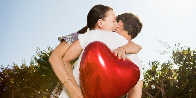 woman grabs heart shaped balloon from man.
