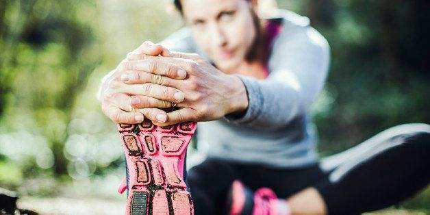 A woman in her early 30's stretches her legs in a bright Pacific Northwest forest after a jog.  Selective focus on her shoe and hands in the foreground.  Horizontal with copy space.