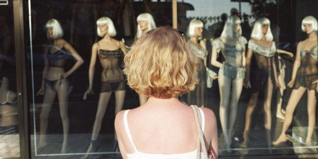 Woman looking at mannequins in store window