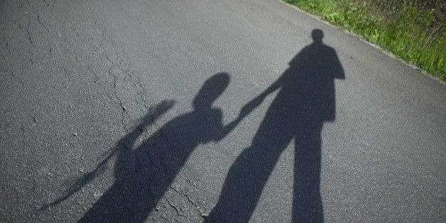 Shadow of father and boy on road