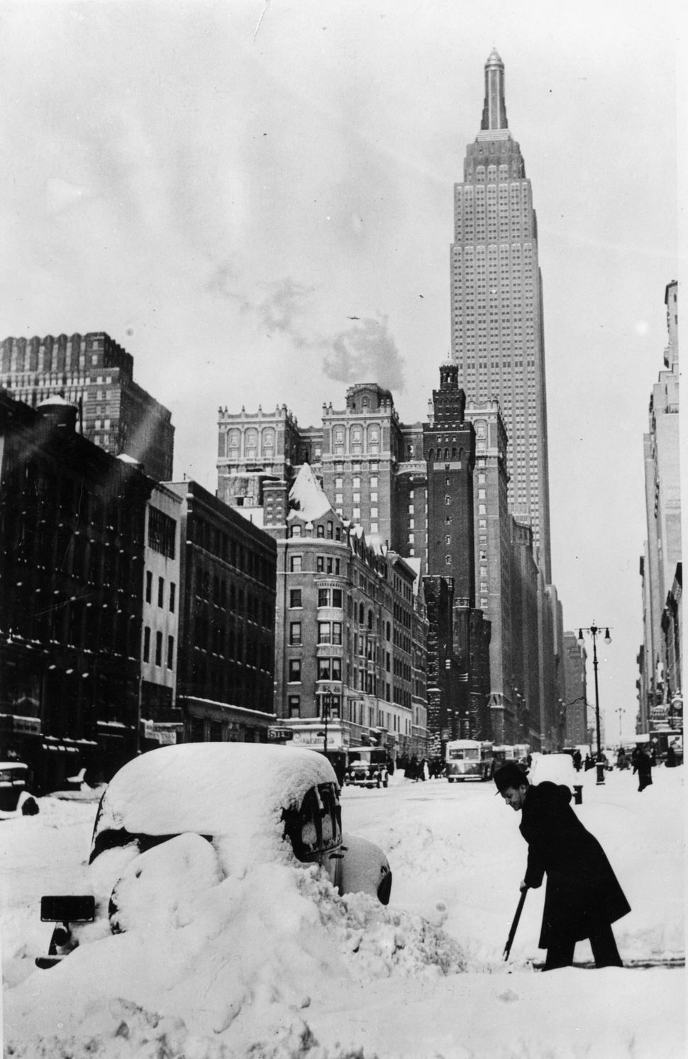 After a surprising snowstorm a driver is clearing the way near the Empire State Building in 1930.