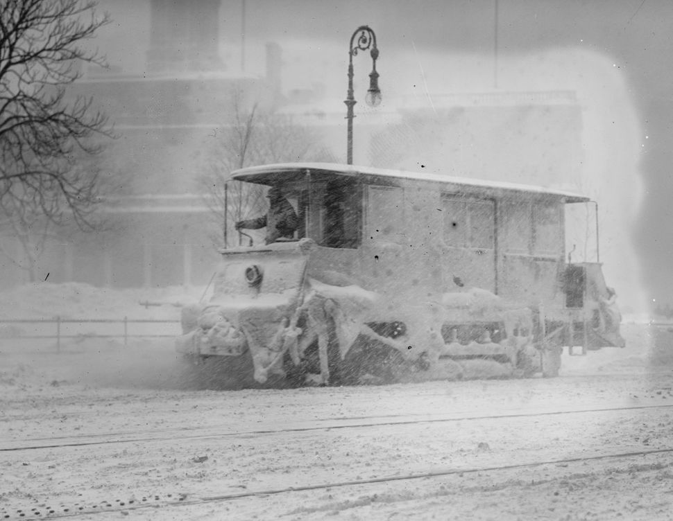 A snow sweeper trolly working during heavy snowfall on New York Streets around 1910.