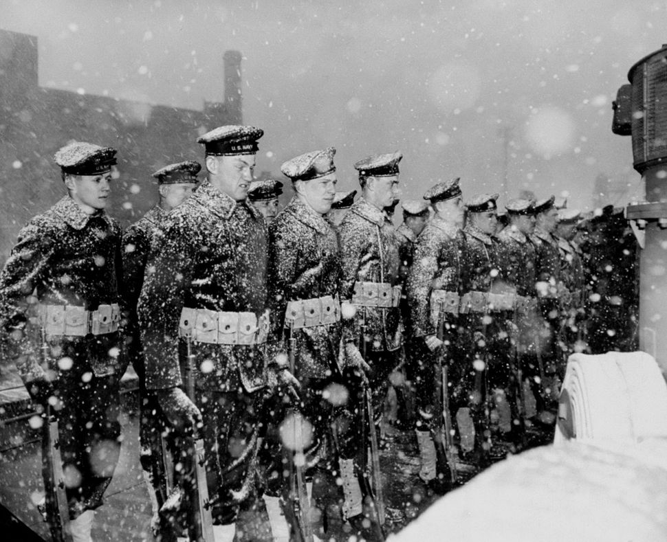 Crew members of the Navy's newest light cruiser, Juneau, is commissioned during a driving snow storm at the Brooklyn Navy Yar