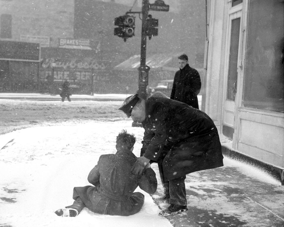 Cop helps fallen man to rise during snowstorm on West Broadway, on Feb. 14, 1940.