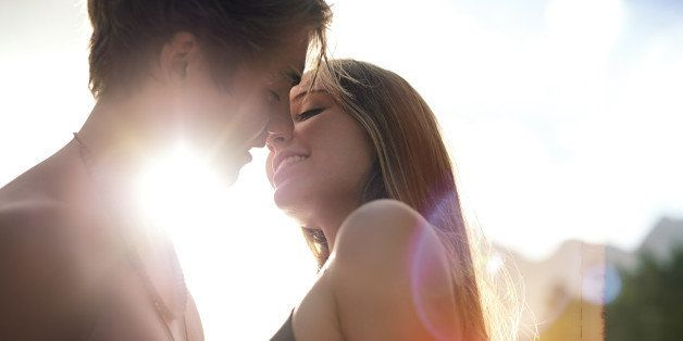 Teenage couple about to kiss with the sun flaring behind them