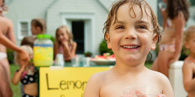little boy holding glass in front of lemonade