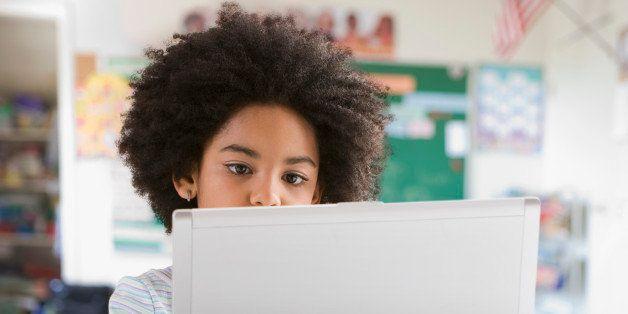 Mixed race girl using laptop